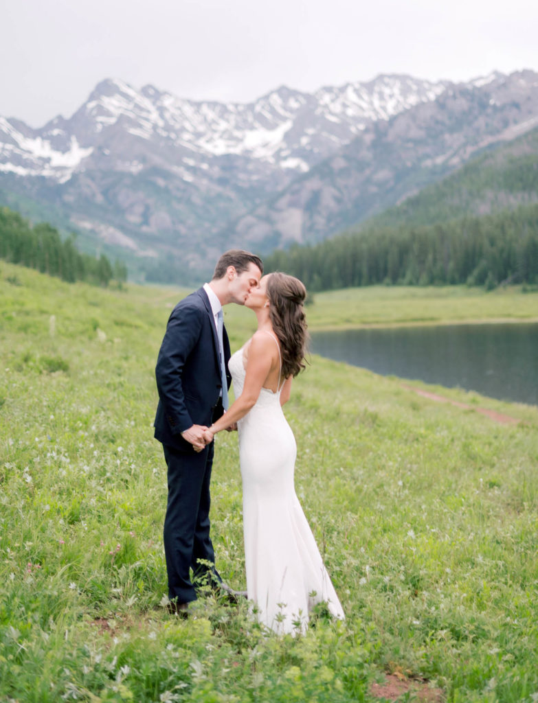 Romantic Mountain Vail Wedding, mountain backdrop, kissing bride and groom, golden hour