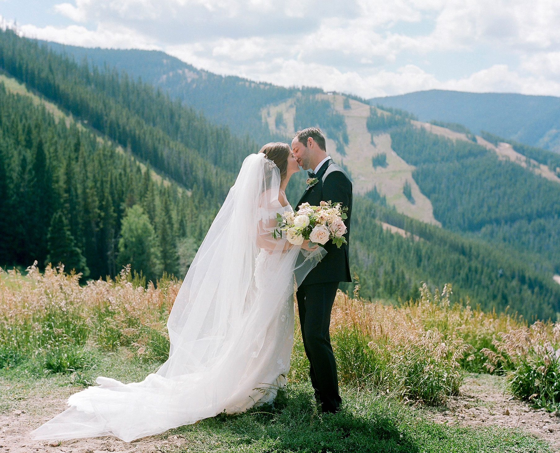Couple kissing with the mountains behind them